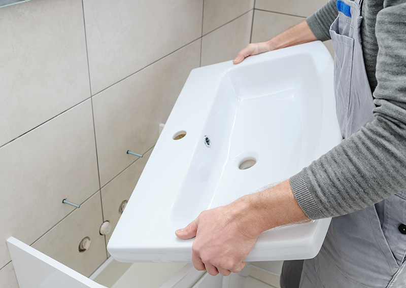 Plumber hanging a new sink onto a bathroom wall