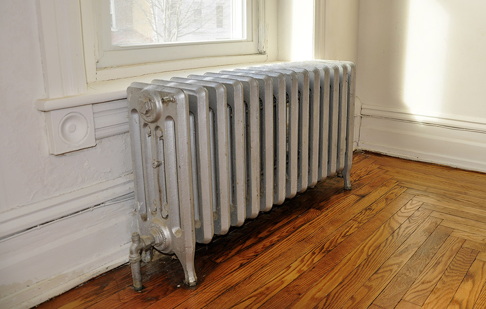 Vintage radiator fitted in a georgian home with a wooden floor